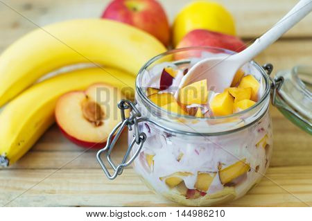 Jar with mixed fruits with fresh homemade yogurt. Fruit salad in a glass container banana apples plum and lemon on background