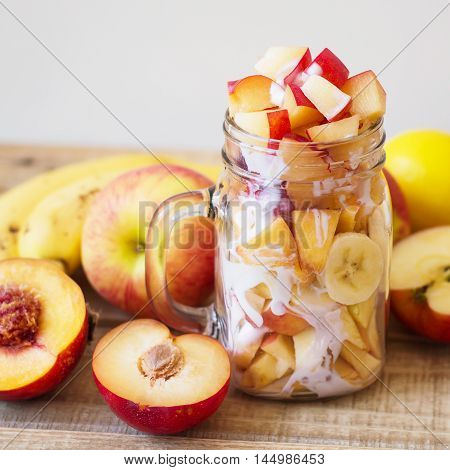 Glass jar with fruit mix and yogurt. Fruit salad made of apple peach nectarine banana lemon slices and yogurt on wooden background. Square format