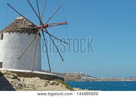 Mykonos, Greece. Traditional windmill with a view to Mykonos island. Over 16 windmills can be found in Mykonos.