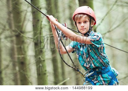 boy at climbing activity in high wire forest park