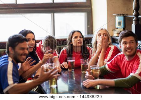 people, leisure, rivalry and sport concept - friends or football fans drinking beer and watching soccer game or match at bar or pub