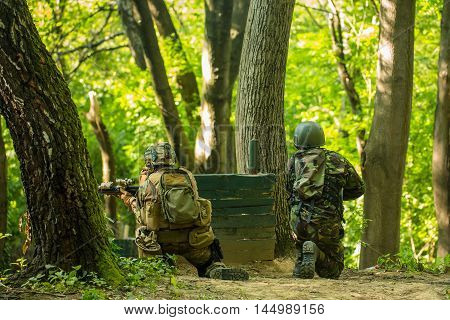 Two soldiers in military uniform ammunition with armed rifle sitting back and shooting near wooden block post and trees in forest