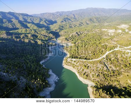 Aerial view of Diarizos river in Paphos Cyprus. The river cutting through the green valley and lush forest of laona mountain leading to the Venetian bridge from the Arminou reservoir.
