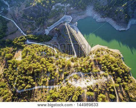 Aerial view of the embankment (earthfill / rockfill) dam in Arminou Paphos Cyprus. A terrain reservoir of the river Diarizos in Pafos cutting through the green valley and lush forest of laona mountain leading to the Venetian bridge. poster