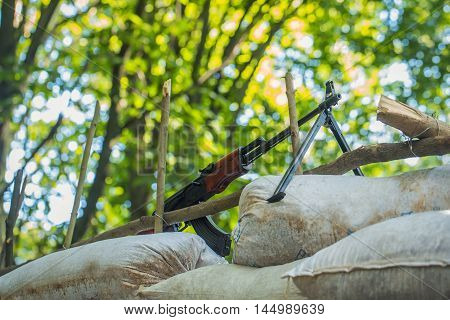 Military rifle standing on sandbags block post in forest on background of green trees