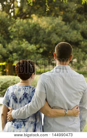 Mother and adult son walking in a park with their arms around each other as the sun is setting casting a golden hue on them.