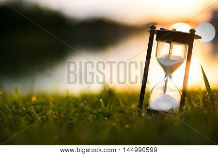 Hourglass on grass field at dawn time