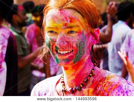 European girl celebrate festival Holi in Delhi India. The main day Holi is celebrated by people throwing coloured powder and coloured water at each other.