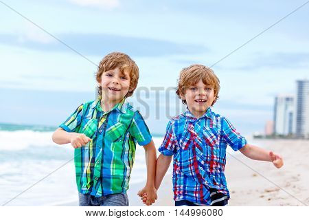 Two happy little kids boys running on the beach of ocean. Funny cute children, sibling and best friends making vacations and enjoying summer.