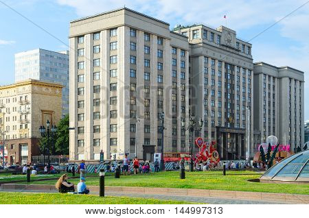 MOSCOW RUSSIA - JULY 23 2016: Unidentified people walk on Manezhnaya Square and Street Okhotny Ryad near building of State Duma of Russian Federation Moscow Russia