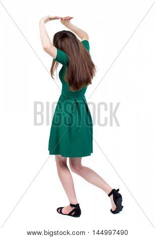 back view of woman protects hands from what is falling from above. The slender brunette in a green short-crossed her arms over her head.