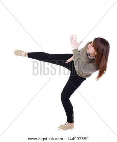 back view of woman funny fights waving his arms and legs. Isolated over white background. A girl in a gray sweater has foot.