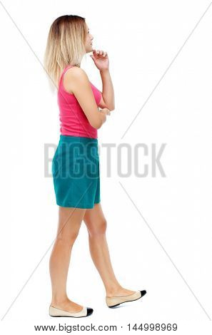 back view of walking woman. beautiful girl in motion. Blonde in a red sweater and green skirt is rubbing his chin thoughtfully.