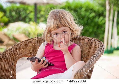 Little Child With Mobile Picking Nose And Looking
