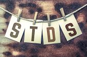 "The word ""STDS"" stamped on cards and pinned to an old piece of twine over a rusted metal background. poster"