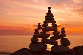 Concept of harmony and balance. Rock Zen at sunset. Balance and poise stones against the sea poster