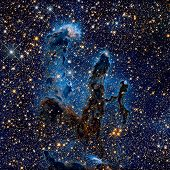 The Pillars of Creation. Infrared view of the Eagle Nebula or M16. It is a young open cluster of stars in the constellation Serpens. Retouched colored image. Elements of this image furnished by NASA. poster