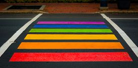 Rainbow colored pedestrian crossing in Moncton, New Brunswick.   Bright, colorfully painted crossing in city of Moncton New Brunswick, Canada.  All inclusive signal.
