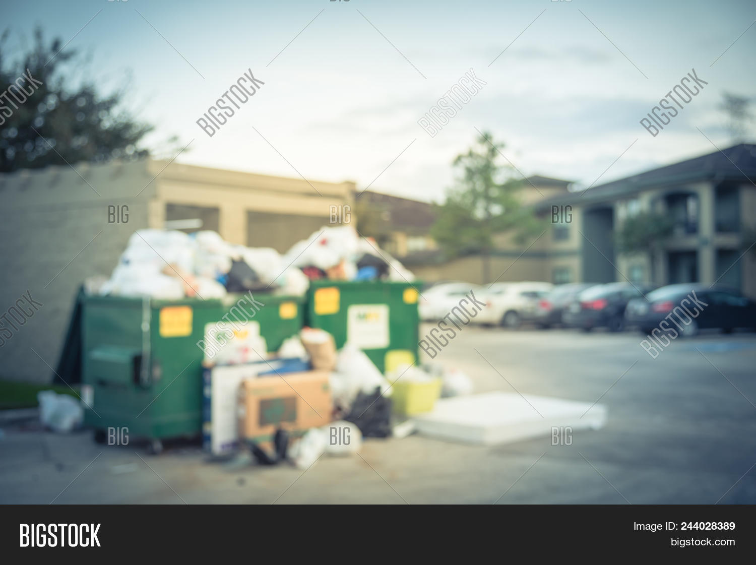 Blurred An Overflowing Dumpster At Apartment Building Yard In Humble Texas Us Overfill And On Ground Full Of Household Waste Plastic Bag Mattress