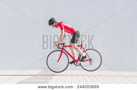 Cyclist In A Helmet And Cycling Clothes Jumps On A Red Road Bike On The Background Of A White Wall.