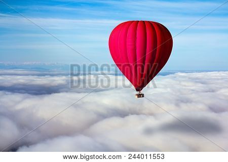 A Lonely Red Hot Air Balloon Floats Above The Clouds. Concept Leader, Success, Loneliness, Victory
