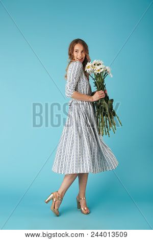 Full length image of Smiling blonde woman in dress posing sideways with flowers and looking away over blue background