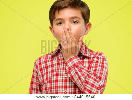 Handsome toddler child with green eyes covers mouth in shock, looks shy, expressing silence and mistake concepts, scared over yellow background