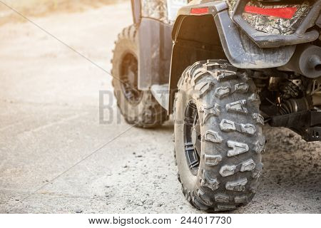 Close-up Tail View Of Atv Quad Bike. Dirty Whell Of Awd All-terrain Vehicle. Travel And Adventure Co