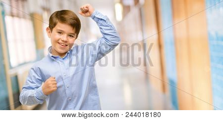 Handsome toddler child with green eyes happy and excited expressing winning gesture. Successful and celebrating victory, triumphant at school corridor