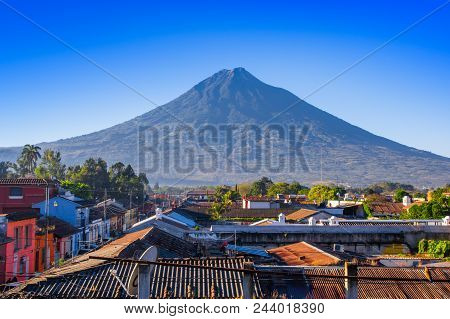 Volcano Agua Above The Roofs Of Old Quarters Of Antigua In A Beautiful Sunny Day And Blue Sky In The