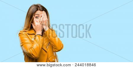 Beautiful young woman smiling having shy look peeking through her fingers, covering face with hands looking confusedly broadly