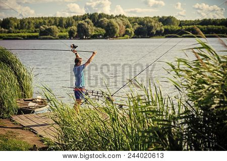 poster of fisherman is fishing on a fishing trip. Fisherman cast fishing rod in lake or river water. Man fish with spinning tackle on wooden pier. Adventure, sport, activity. Spin fishing, angling, catching fish. Hobby, vacation, pastime.