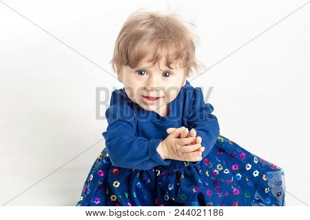Portrait Of Happy Baby Girl 1 Year Old With Blue Eyes And Dress Posing In Studio. White Background.