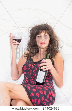 Upset Mature Woman In Nightie Drinking Wine In Her Bedroom