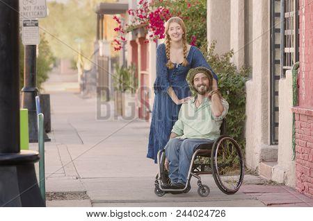 Woman In Blue Dress With Friend In Wheelchair On Sidewalk