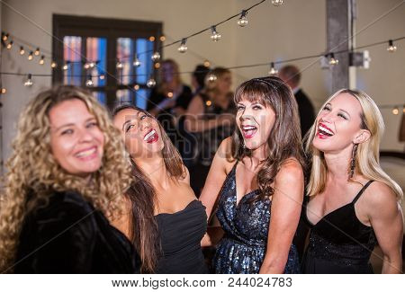 Four Mature Women Laughing Loudly At A Party