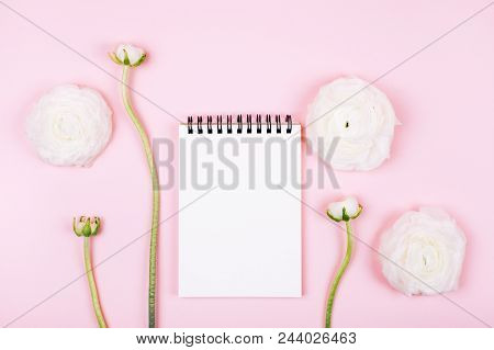 Notebook With Clean Page With Beautiful Spring Ranunculus Flowers On Pink Pastel Background. Top Vie