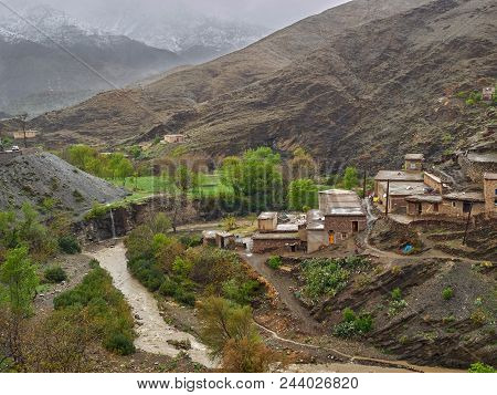 Traditional Berber Village Of Clay Houses With Flat Roofs On A Hillside Near The River, The High Atl