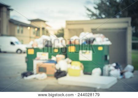 Vintage Blurred Overflowing Dumpster At Apartment Building In Usa