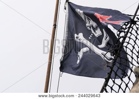 Pirate Flag Fluttering In The Wind On A Mast Of A Pirate Ship Replica, Penzance Harbour, Cornwall, E