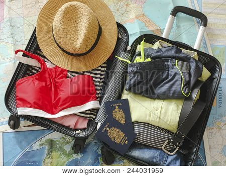 Open Traveler's Bag With Clothing, Accessories, And Passport. Travel And Vacations Concept