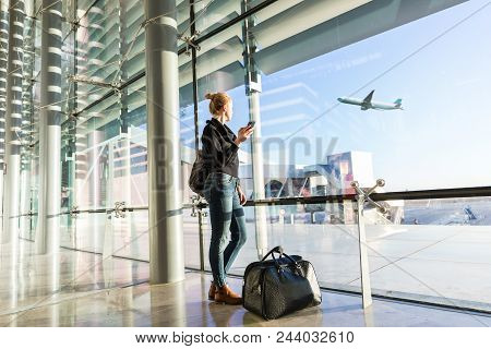 Young Casual Female Traveler At Airport, Holding Smart Phone Device, Looking Through The Airport Gat