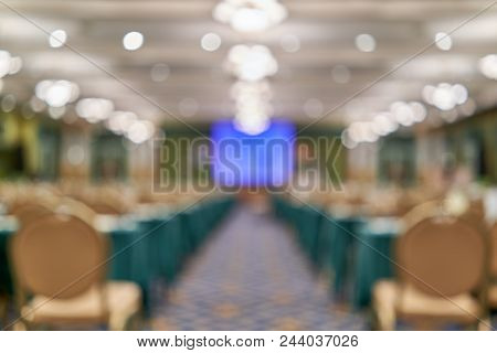 Blur Blue Screen Projector On Stage With Green Table And Gold Chair In Conference Room Use As Backgr