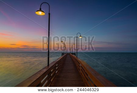 First Light: The Night Lights Still On Over The Fishing Pier As The Sunrises Over The Atlantic Ocean