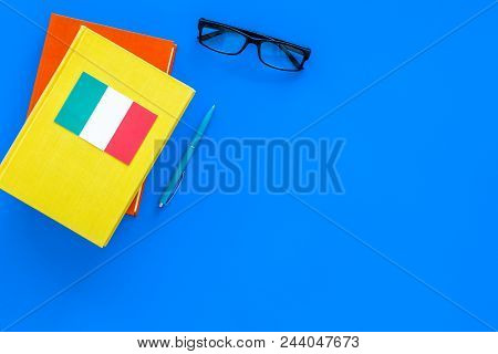 Language Study Concept. Textbooks Or Dictionaries Of Foreign Language Near Italian Flag On Blue Back
