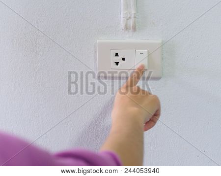 Close Up Female Hand Turning On Or Off On Grey Light Switch With Texture Background. Turning Light C