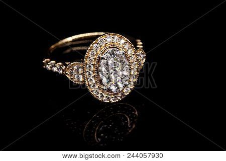 An ornate halo design diamond cocktail ring set in 18 carat yellow gold isolated on a black background poster