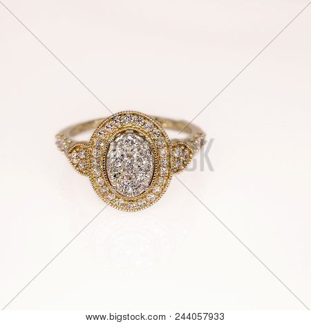An ornate and decorative halo designed diamond cocktail ring set in 18 carat gold isolated on a white background poster