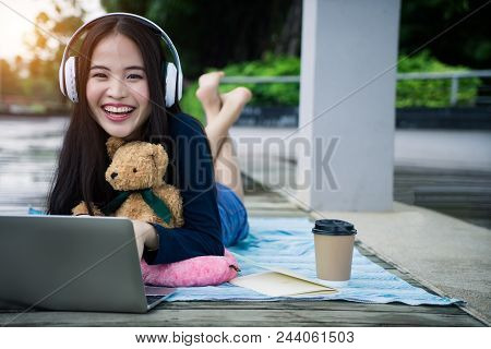 Happy Woman Lying Down Working With Laptop Computer. Attractive Young Student Girl Watching Media On