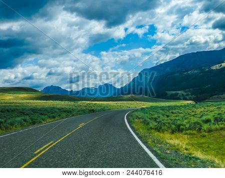 Paved Road In The Yellowstone National Park, Wyoming, United States, Between Prairies, Mountains And